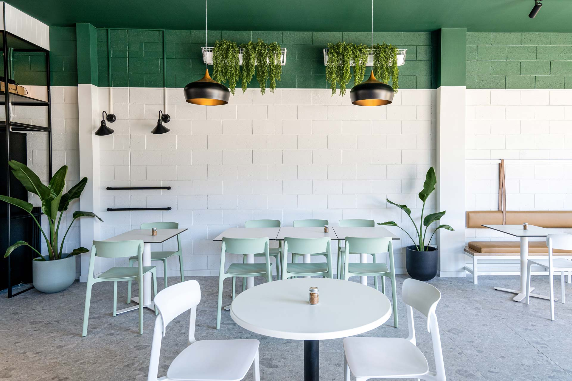 Forklore cafe fitout with a green ceiling, plants and pastel tables and chairs