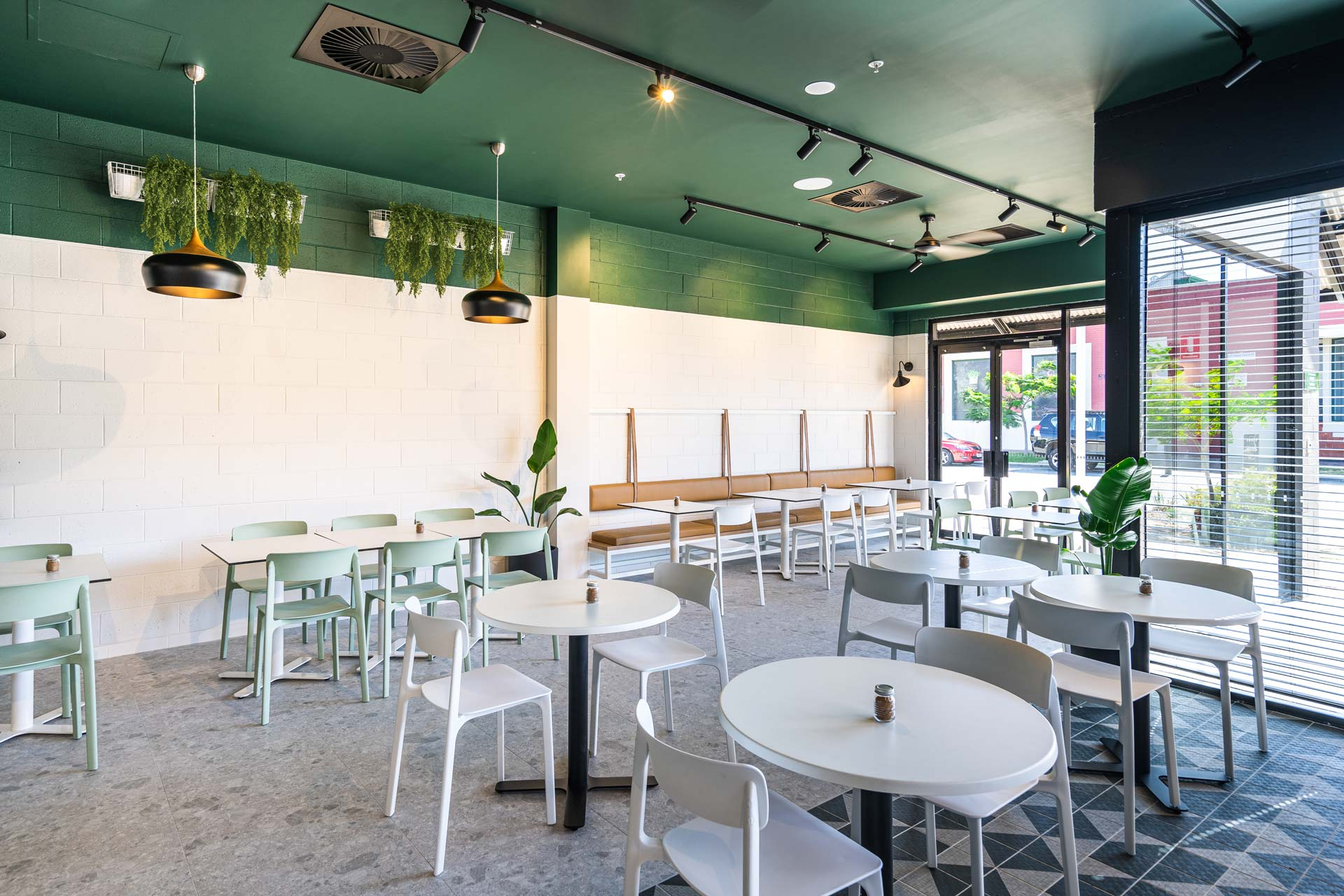 Forklore cafe fitout with white tables and chairs and a green ceiling