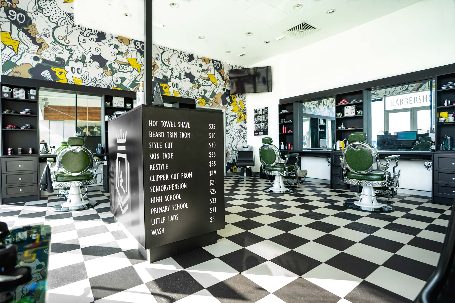 Barbers fitout with chequered flooring, jazzy wallpaper and barber chairs