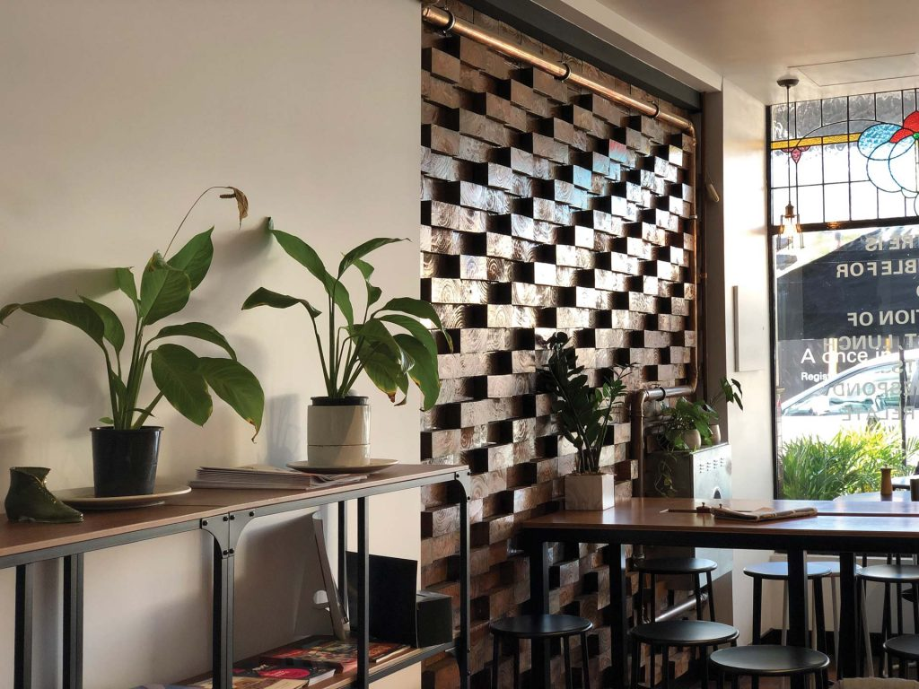 Trendy café filled with bar tables and stools with lots of indoor plants